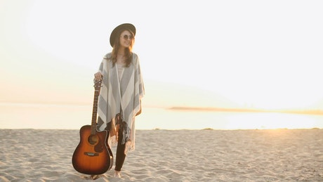Young hipster woman on beach with acoustic guitar