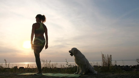 Young lady doing Yoga outside with her dog