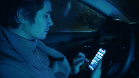 Young male driver scrolling on his Smartphone