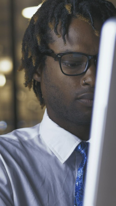 Young man adjusting his glasses while working on computer