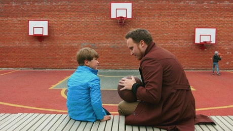 Young man and his little brother on the basketball playground