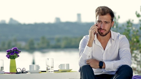 Young man at a table outdoors on a call