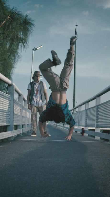Young man dancing upside down on a pedestrian bridge