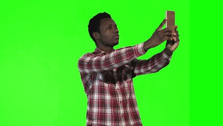 Young man doing a selfie on a green screen