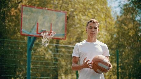 Young man dribbling a basketball facing the lens