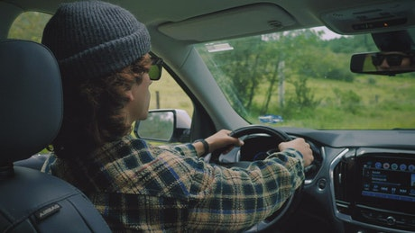 Young man driving during a road trip through nature
