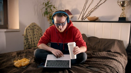 Young man eating snacks browsing the internet