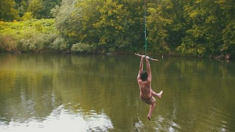 Young man enjoying a lake swing