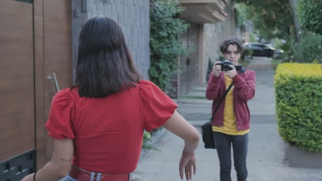 Young Man filming a girl dancing in the street