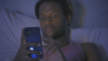 Young man lying on his bed checking his smartphone