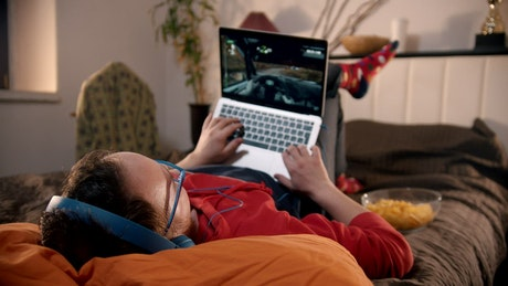 Young man lying on the bed playing video games on a laptop