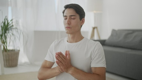 Young man meditating in the living room