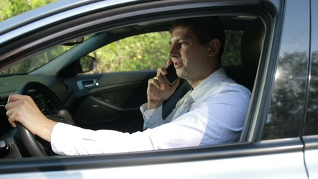 Young man on a car talking on cell phone