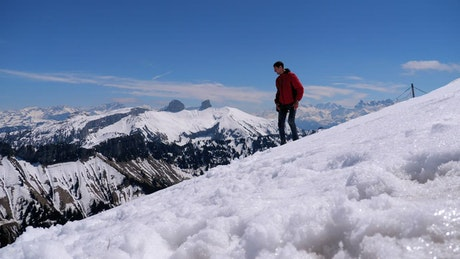 Young man on the top of a snowy mountain