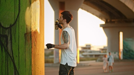 Young man painting a graffiti with a spray