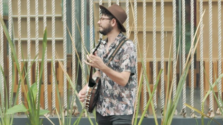 Young man playing and singing with a banjo in a garden