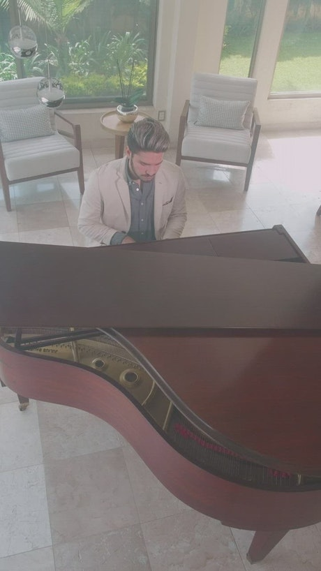 Young man playing the piano in a stylish lobby