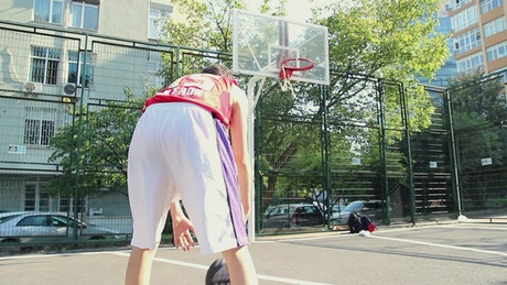 Young man practicing basketball on a court