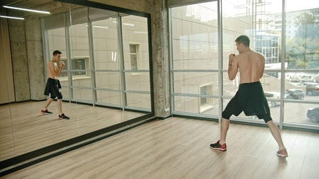 Young man practicing martial arts in a mirror