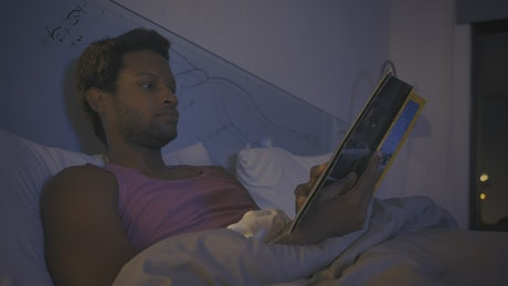 Young man reading a book before going to sleep