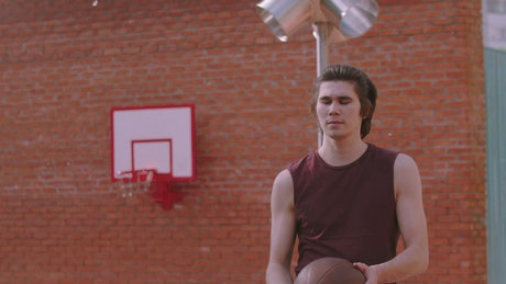Young man spinning  a basketball ball on the finger