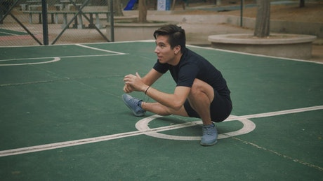 Young man stretching on the court in a park
