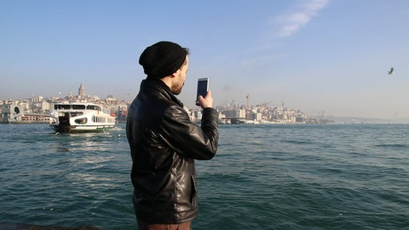 Young man taking photos on a sunny shore