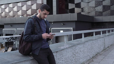 Young man texting in the city