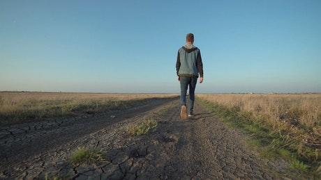 Young man walking in a rural path