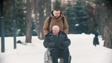 Young man walking with grandfather in a wheelchair