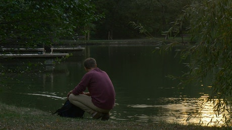 Young man walks away from a lake after appreciating it