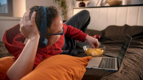 Young man watching videos and eating snacks