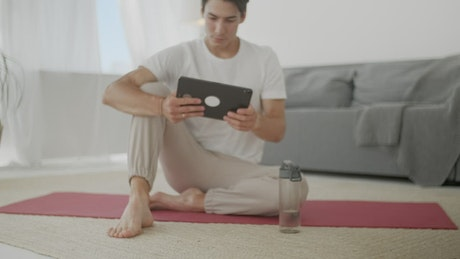 Young man watching yoga videos for practice