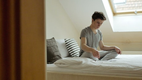 Young man with earphones meditating on the bed
