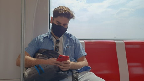 Young man with mask traveling by subway with his cellphone