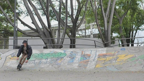 Young man with roller skates sliding down ramps with graffiti