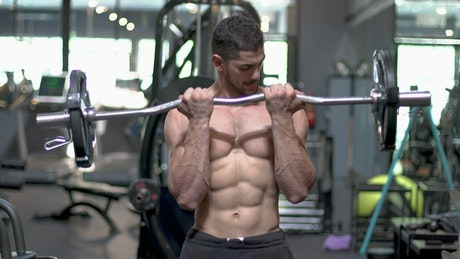 Young man working out with a dumbbell in a gym