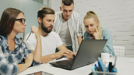 Young marketing team gather around laptop