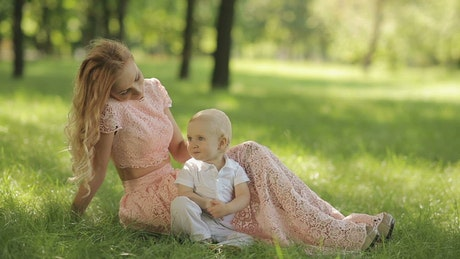 Young mother caresses her son in the park