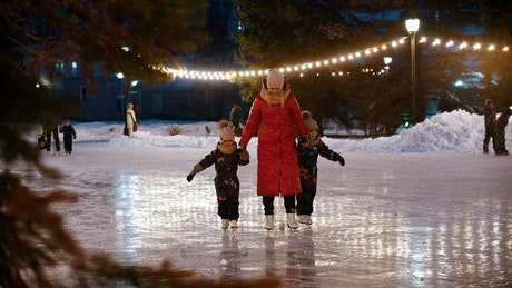 Young mother doing ice skating with her children