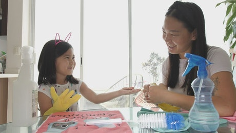 Young mother putting cleaning gloves on her daughter
