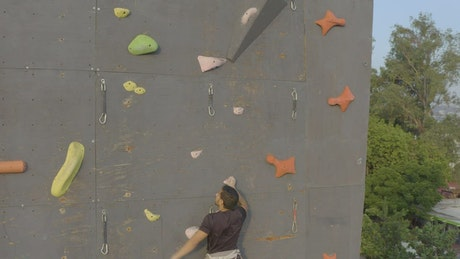 Young mountaineer climbing a large wall for mountaineering