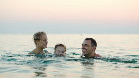 Young parents playing in the ocean