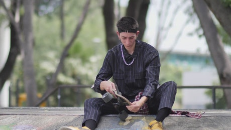 Young skateboarder sitting placing his skateboard aside