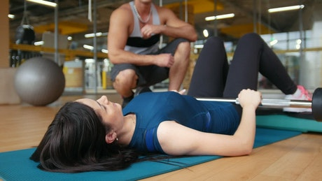 Young Slim woman doing exercise with a personal trainer