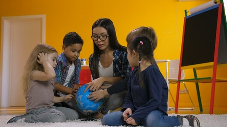 Young teacher teaching geography to a few children
