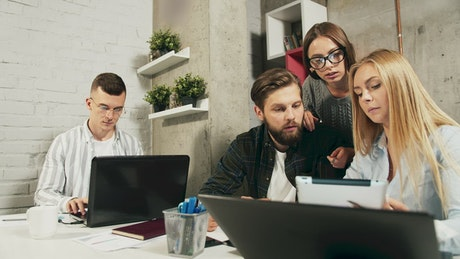 Young team brainstorms ideas while working in modern office