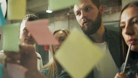 Young team brainstorms ideas with sticky notes