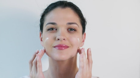 Young woman applying skin care cream on face
