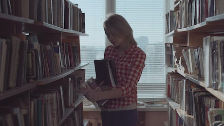 Young woman arranging the books at the library
